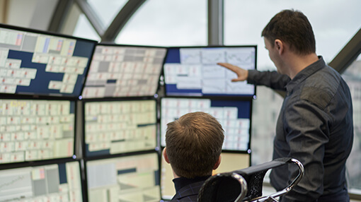 Traders discussing information on bank of computer screens