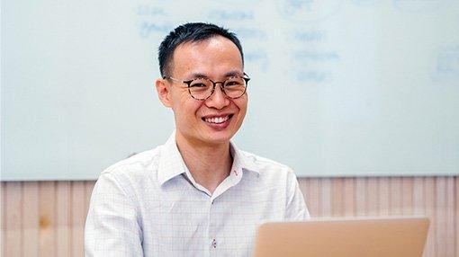 Man smiling from behind laptop